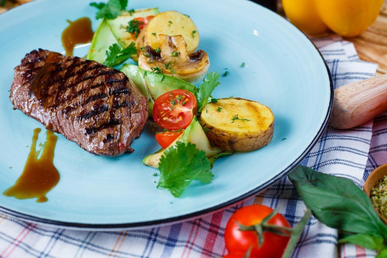 Стейк из мяса страуса с овощами гриль,малиновым соусом.