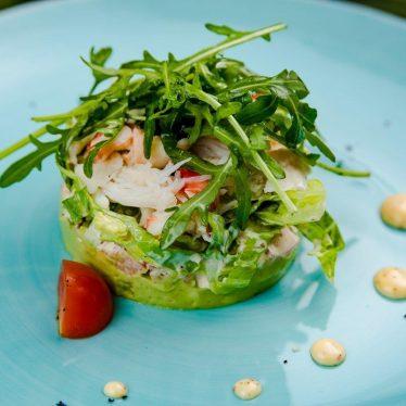 Салат с мясом краба на подушке из авокадо.